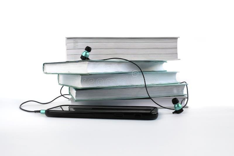 Concepto a escuchar los audiolibros Auriculares y smatphone azules cerca de la pila de libros libre illustration