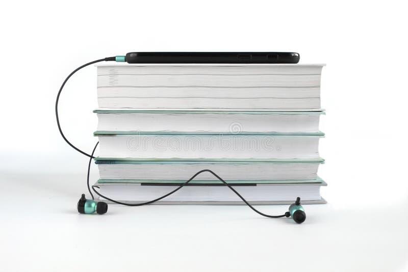 Concepto a escuchar los libros audios Auriculares azules cerca de la pila de libros Fondo blanco con el espacio de la copia para  stock de ilustración