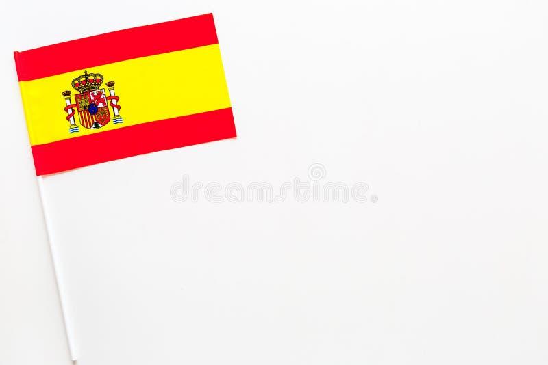 Concepto español de la bandera pequeña bandera en el espacio blanco de la copia de la opinión superior del fondo fotografía de archivo libre de regalías