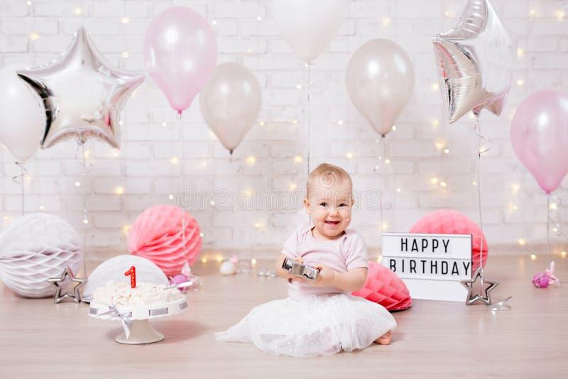 Concepto estrellado del partido - muchacha feliz y torta rota sobre la pared de ladrillo con las luces y los globos imágenes de archivo libres de regalías