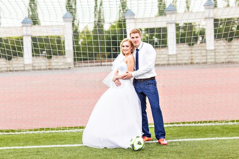 Concepto europeo del campeonato del balompié Pares de la boda en el estadio de fútbol imagenes de archivo