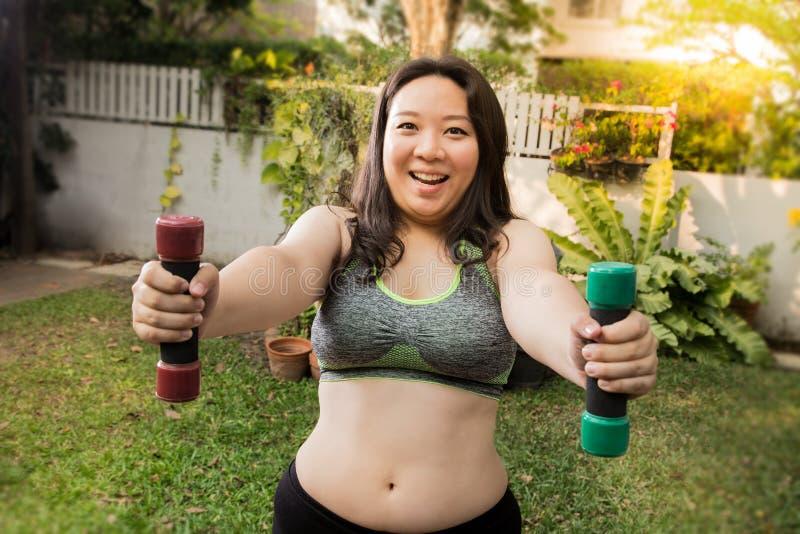 Concepto feliz de la pérdida de peso del ejercicio de la cara de la diversión de la mujer gorda en casa con pesa de gimnasia de l imagen de archivo