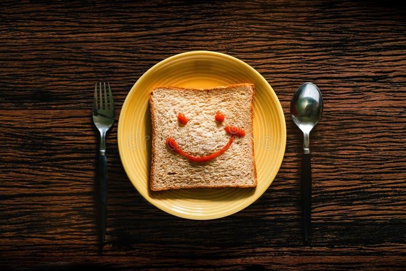 Concepto feliz de la vida Pan en la placa con la cuchara y bifurcación por tiempo de desayuno Cara sonriente dibujada en el pan fotos de archivo libres de regalías