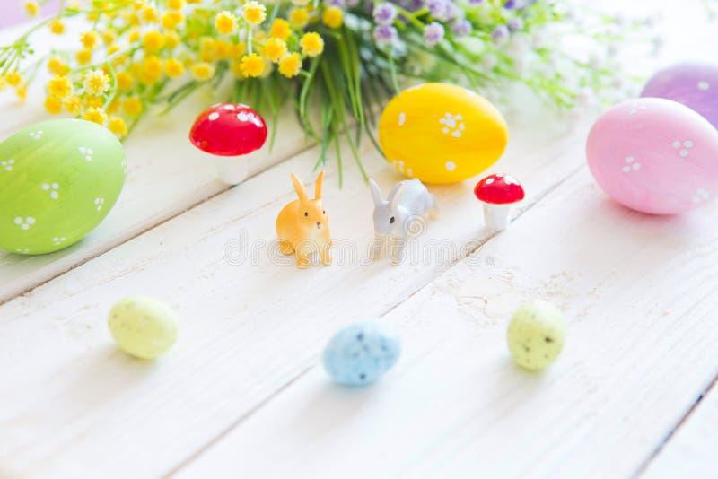 Concepto feliz de Pascua La tarjeta de felicitación de Pascua con las flores, conejito de los conejos de pascua juega y eggs en e fotografía de archivo