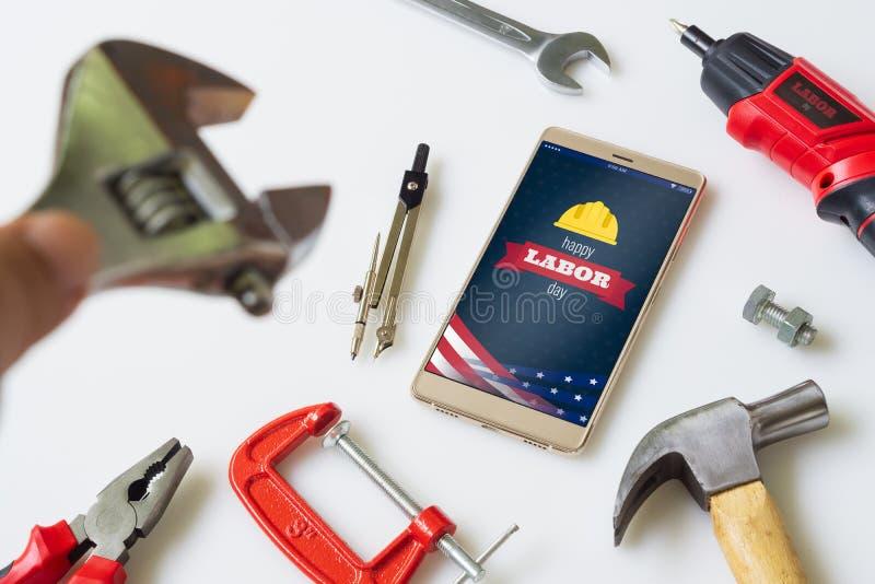 Concepto feliz del fondo del D?a del Trabajo Teléfono móvil puesto plano con día de fiesta feliz de los E.E.U.U. del Día del Trab foto de archivo libre de regalías