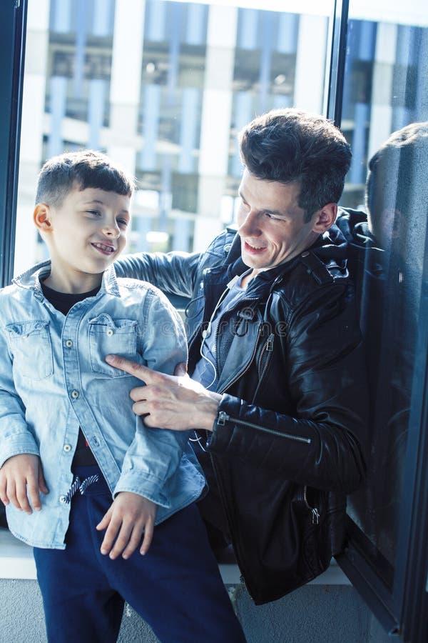 Concepto feliz, padre e hijo de la familia junto en los huggings de la ventana, disfrutando de luz del sol, gente de la forma de  fotos de archivo libres de regalías