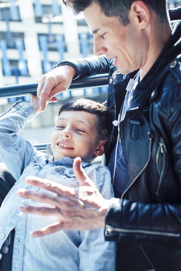 Concepto feliz, padre e hijo de la familia junto en los huggings de la ventana, disfrutando de luz del sol, gente de la forma de  imagen de archivo libre de regalías