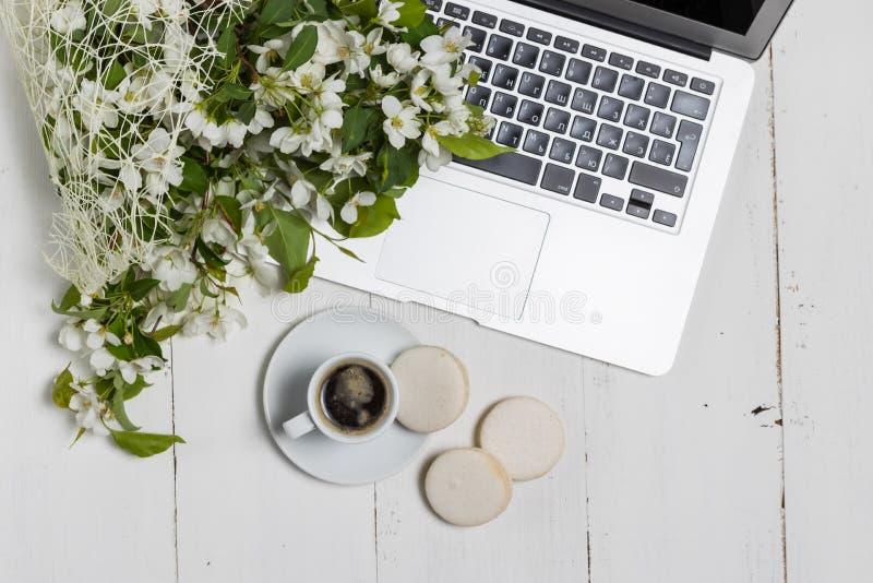 Concepto femenino del negocio con el ordenador portátil, el ramo de las flores de la primavera y las manos de la mujer sosteniend imagenes de archivo