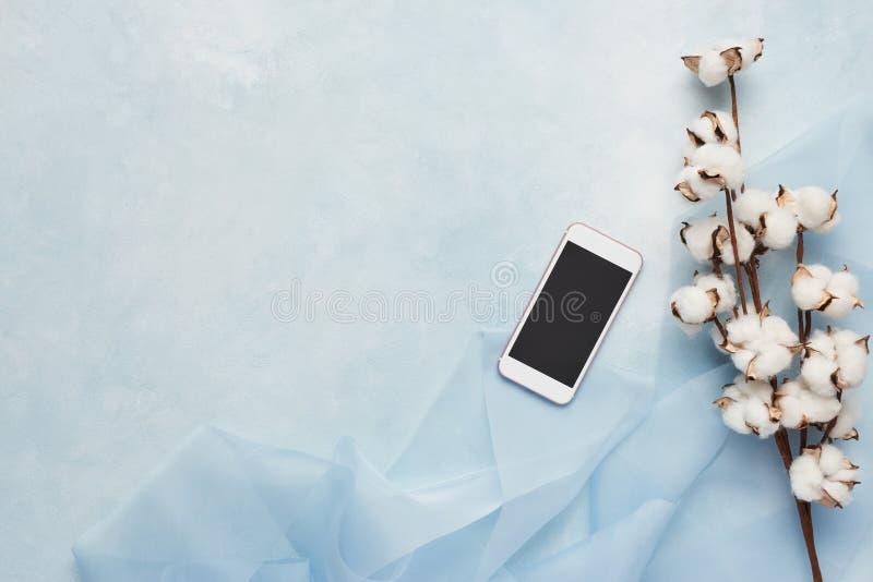 Concepto femenino: fondo azul claro con el teléfono celular, seda imagen de archivo