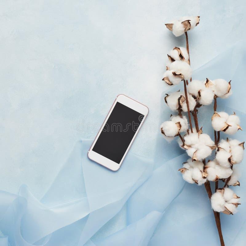 Concepto femenino: fondo azul claro con el teléfono celular, seda foto de archivo libre de regalías