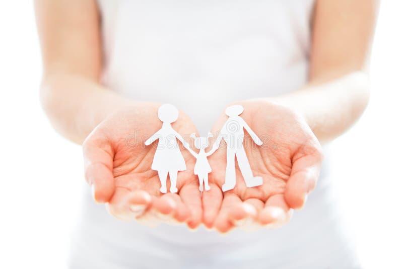 Concepto. figuras de papel de la familia en manos fotos de archivo libres de regalías