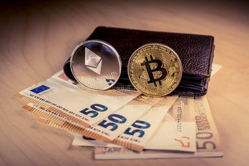 Concepto financiero con el bitcoin físico y ethereum sobre una cartera con las cuentas euro fotografía de archivo libre de regalías