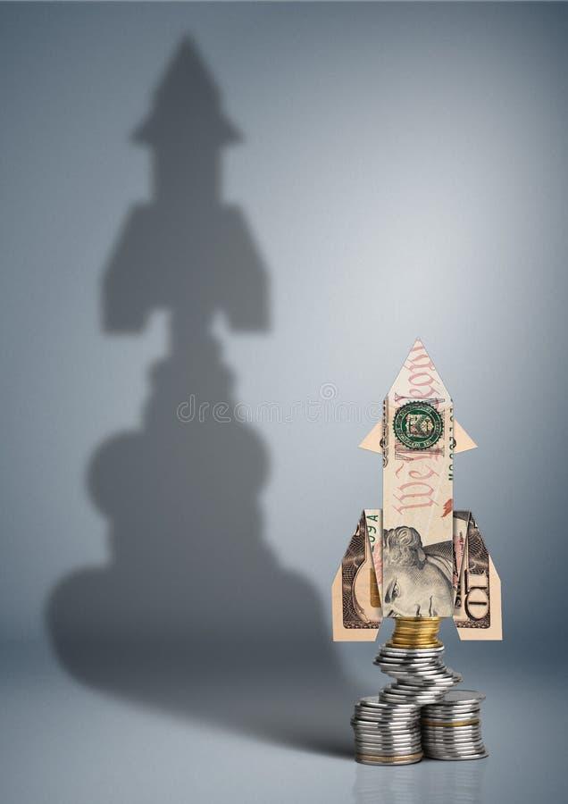 Concepto financiero del aumento de beneficios, dinero con la sombra del cohete foto de archivo