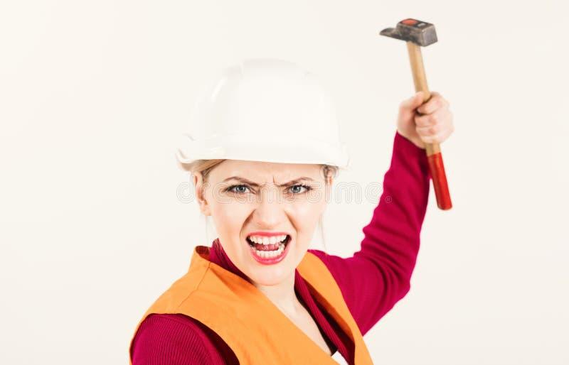 Concepto fuerte y independiente La mujer joven trabaja como constructor La mujer con la cara de grito sostiene el martillo, aisla imagen de archivo