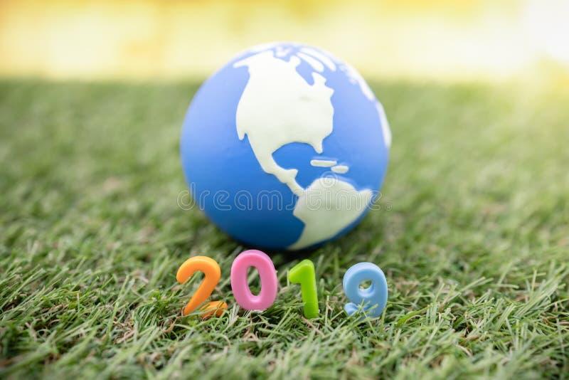 Concepto global 2019 del Año Nuevo Ciérrese para arriba de número plástico colorido del juguete en hierba con la mini bola del mu foto de archivo libre de regalías