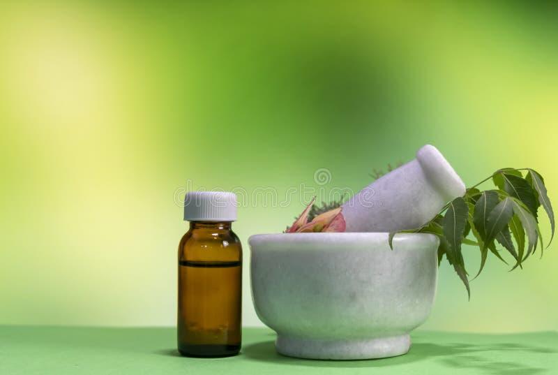 Concepto homeopático clásico - hierbas de curación, flor rosada en mortero con la sustancia homeopática en botella marrón en amar fotografía de archivo