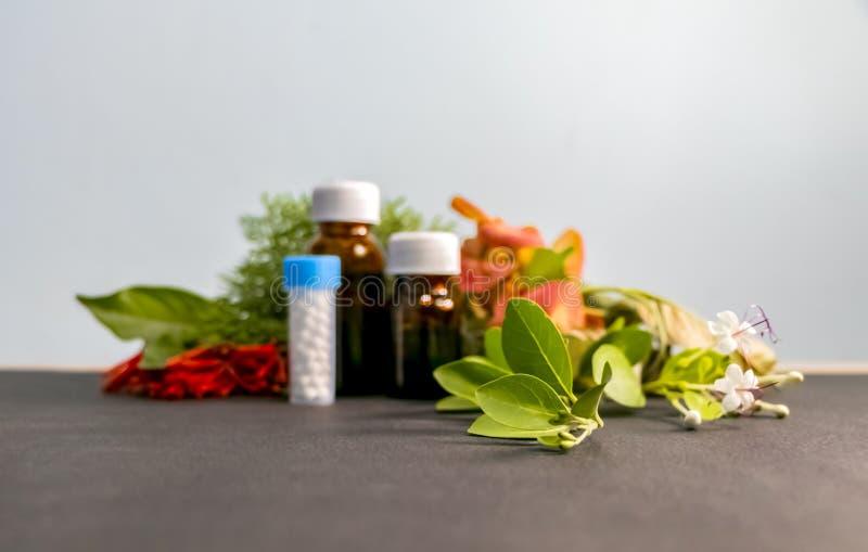 Concepto homeopático - imagen borrosa de las botellas de la medicina homeopática con las flores blancas, rojas, anaranjadas y las fotos de archivo