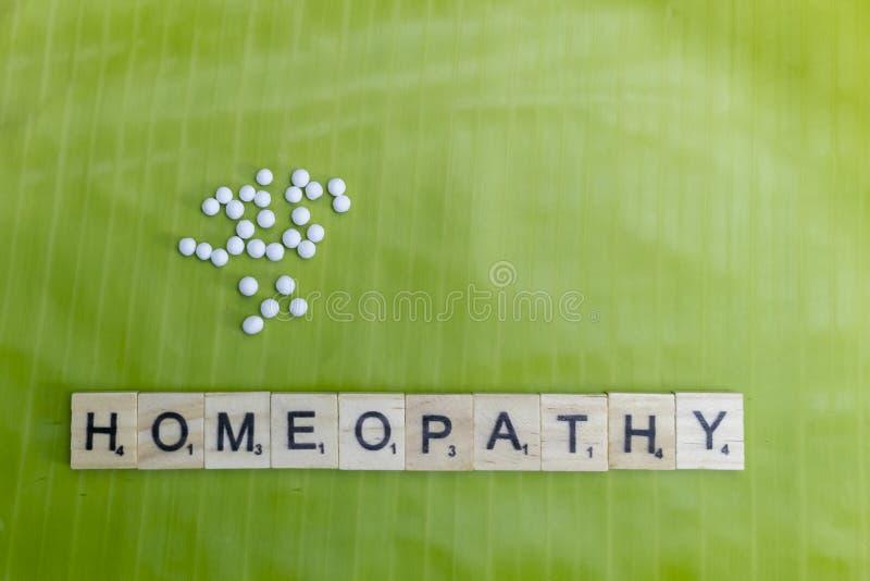 Concepto homeopático natural - píldoras dispersadas de la medicina homeopática en la hoja del plátano con el texto de la homeopat imagenes de archivo