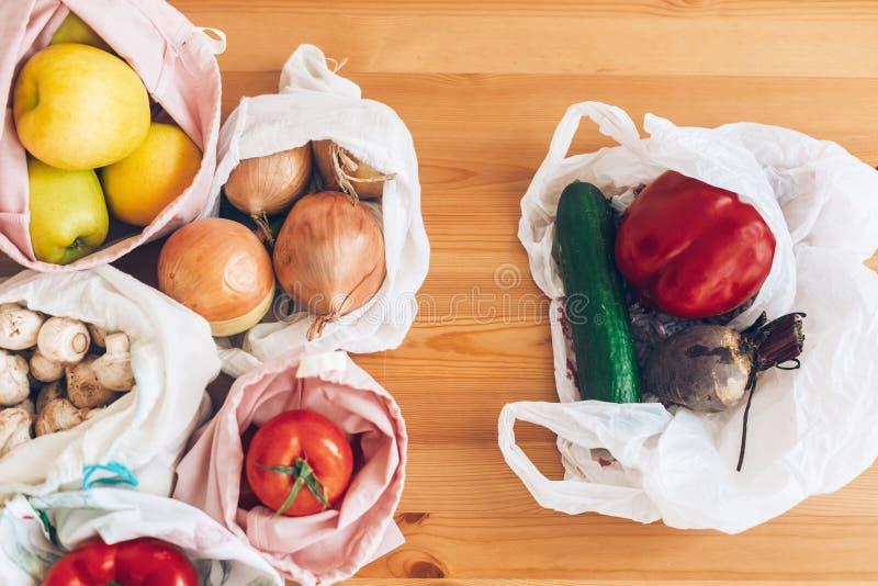 Concepto inútil cero de las compras Ultramarinos frescos en bolsos reutilizables del eco y verduras en bolso de polietileno plást fotos de archivo libres de regalías