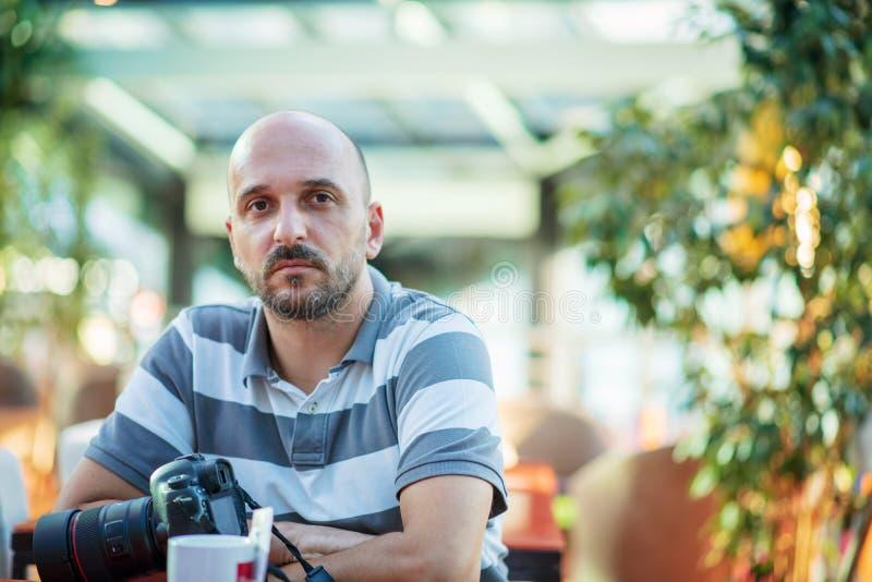 Concepto independiente Fot?grafo profesional Hombre barbudo joven usando el ordenador port?til mientras que se sienta en terraza  imagenes de archivo