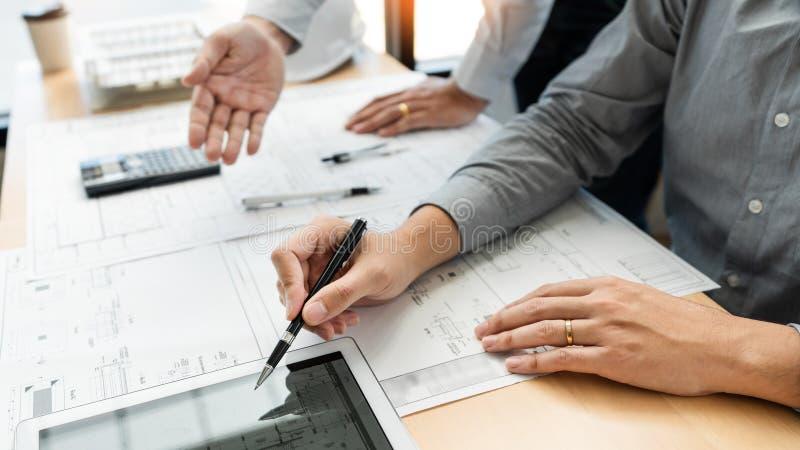 Concepto inmobiliario, dos ingeniero y arquitecto que discute el trabajo de los datos de los modelos y la tableta digital en el e foto de archivo libre de regalías