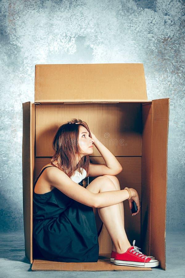 Concepto introvertido Mujer que se sienta dentro de la caja y que trabaja con el teléfono foto de archivo