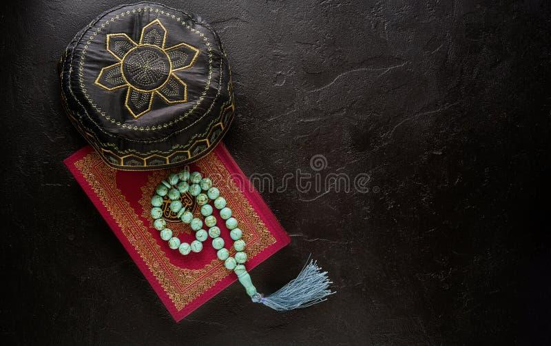 Concepto isl?mico Composición puesta plana del libro sagrado para el Quran, las gotas musulmanes del rosario y rogar el sombrero fotos de archivo