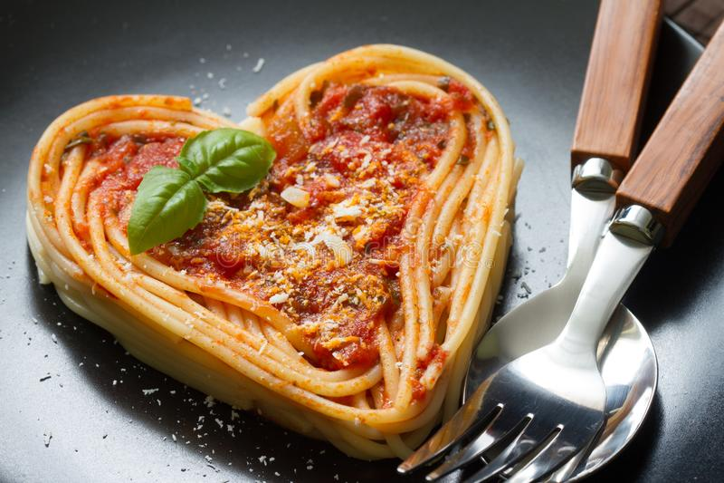 Concepto italiano del extracto de la dieta del amor del corazón de las pastas de los espaguetis en fondo negro imágenes de archivo libres de regalías