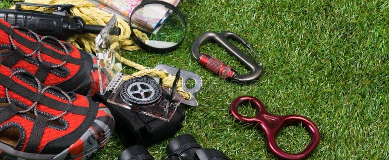 Concepto largo de acampar Caminando en las montañas y el turismo, un sistema de cosas al alza en un fondo de la hierba verde fotos de archivo libres de regalías