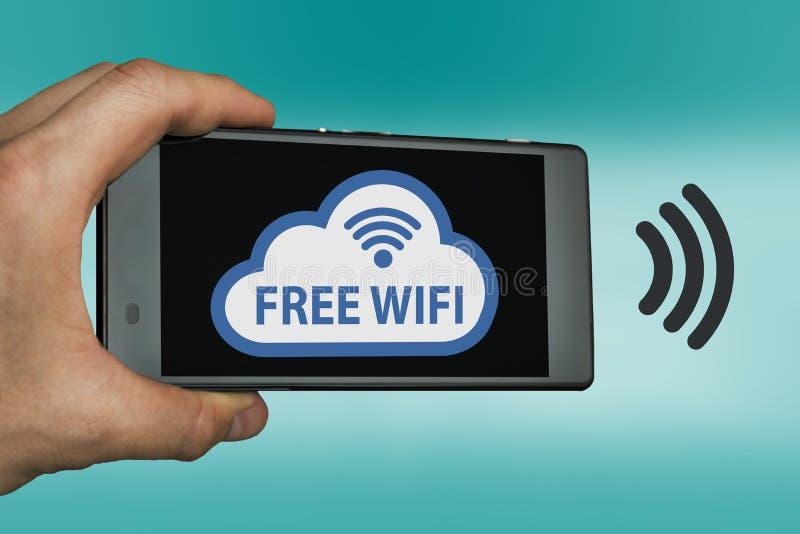 Concepto libre de WIFI con la mano que lleva a cabo el dispositivo móvil imagenes de archivo