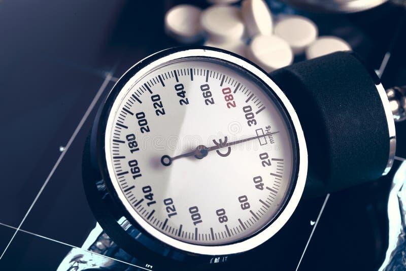 Concepto médico con el indicador y las píldoras de la presión arterial fotos de archivo