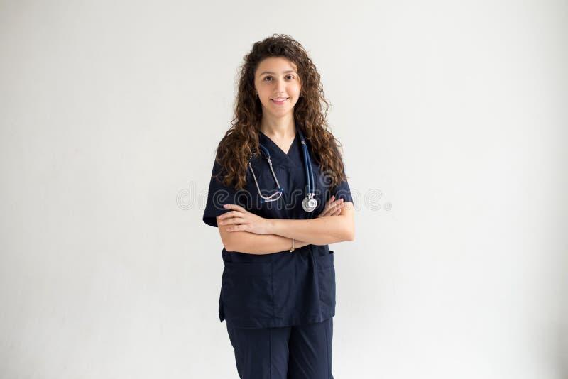 Concepto médico de doctor de sexo femenino hermoso joven en capa azul Trabajador del hospital de la mujer que mira la cámara y qu fotos de archivo libres de regalías