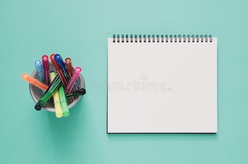 Concepto mínimo del lugar de trabajo de la oficina Pluma en blanco b del cuaderno y del color foto de archivo libre de regalías