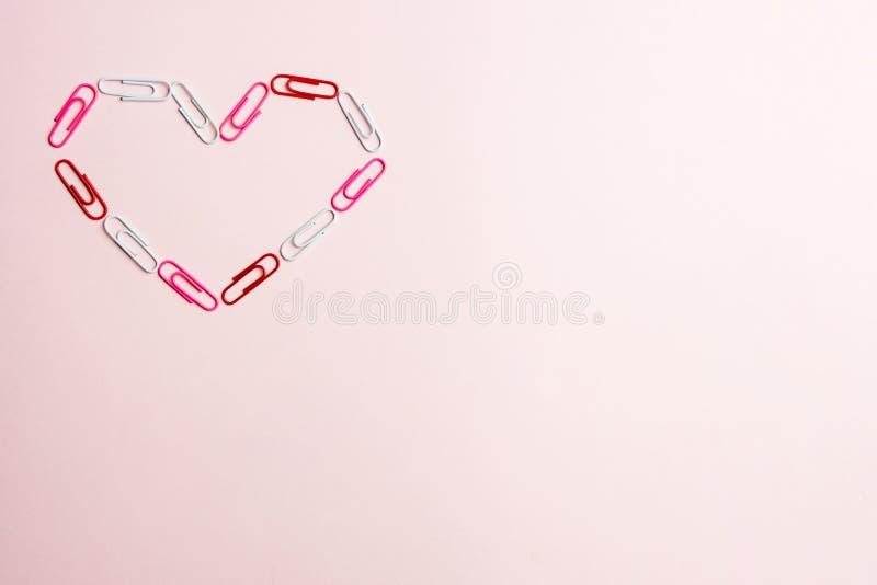 Concepto mínimo El símbolo del corazón hecho de los efectos de escritorio acorta en fondo rosado Endecha plana, visión superior ilustración del vector
