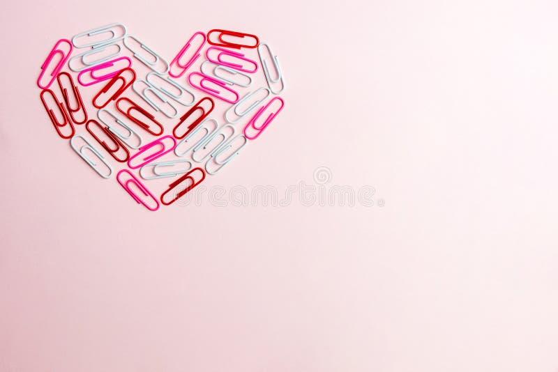 Concepto mínimo El símbolo del corazón hecho de los efectos de escritorio acorta en fondo rosado Endecha plana, visión superior stock de ilustración