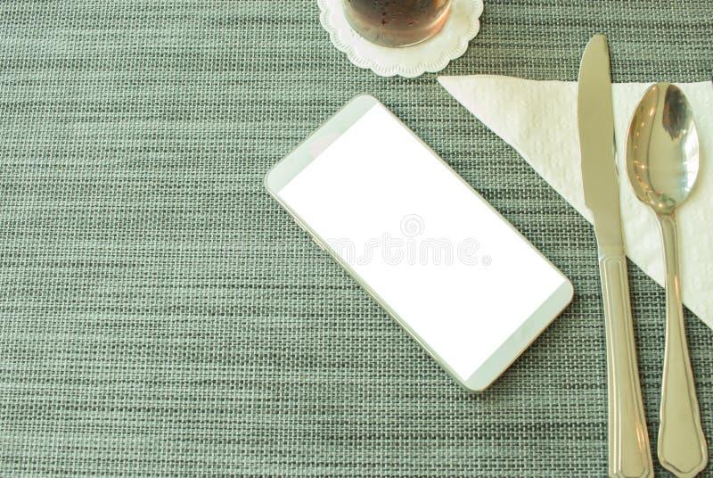 Concepto móvil de Smartphone: Vista superior de la mofa encima del teléfono elegante con la cuchara y de la bifurcación en el man fotografía de archivo libre de regalías