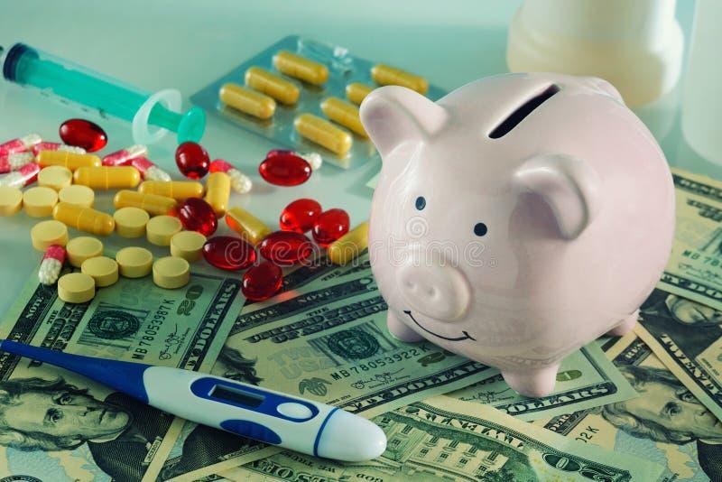 Concepto, medicina costosa En la hucha, el dinero y la medicina del cerdo de la imagen Se dispersan las píldoras rojas y amarilla fotos de archivo