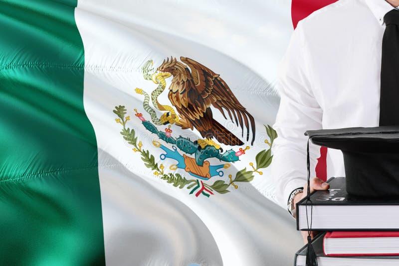 Concepto mexicano acertado de la educación del estudiante Sostener los libros y el casquillo de la graduación sobre fondo de la b imagen de archivo