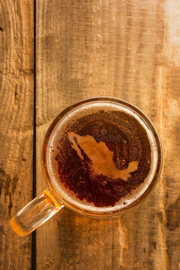 Concepto mexicano de la cerveza, silueta de México en espuma en vidrio de cerveza en la tabla de madera foto de archivo libre de regalías