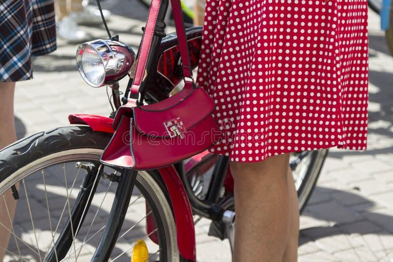 Concepto: mujeres en las bicicletas Una muchacha con una bicicleta, llevando una falda roja del lunar y un bolso rojo Parte de la imágenes de archivo libres de regalías