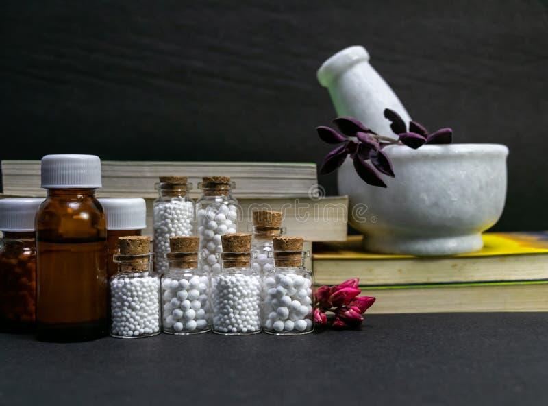 Concepto natural de la homeopatía – hierbas de curación en un mortero y una maja al lado de la medicina homeopática que consiste  fotografía de archivo