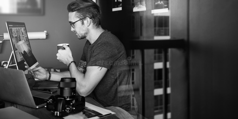 Concepto ocupado de Editing Home Office del fotógrafo del hombre imagen de archivo