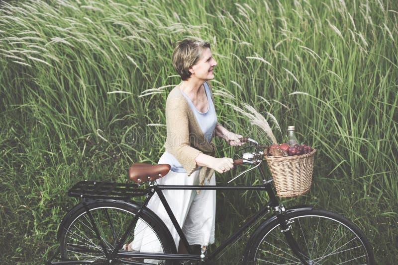 Concepto pacífico de la frescura despreocupada mayor de la bicicleta de la mujer imagen de archivo