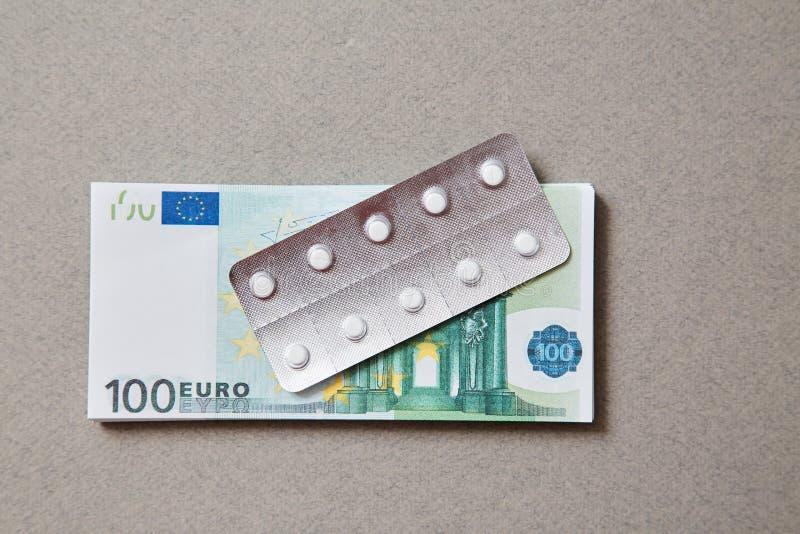Concepto para la medicina costosa de la atención sanitaria, farmacéutica y pagada La botella de píldoras en las notas foto de archivo libre de regalías