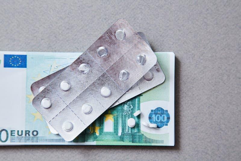 Concepto para la medicina costosa de la atención sanitaria, farmacéutica y pagada La botella de píldoras en las notas imagenes de archivo