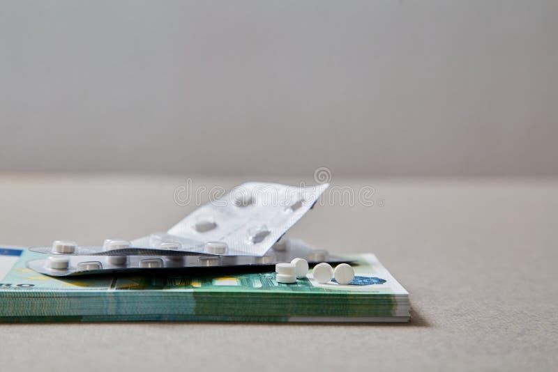 Concepto para la medicina costosa de la atención sanitaria, farmacéutica y pagada Tabletas que mienten en un paquete de billetes  imagen de archivo