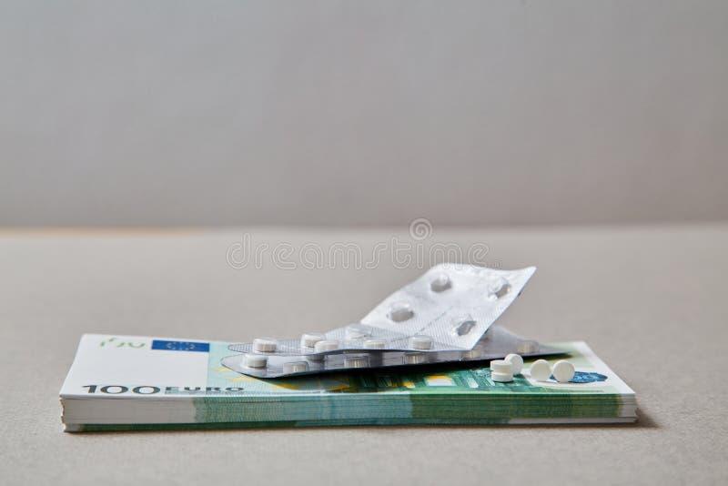 Concepto para la medicina costosa de la atención sanitaria, farmacéutica y pagada Tabletas que mienten en un paquete de billetes  fotografía de archivo