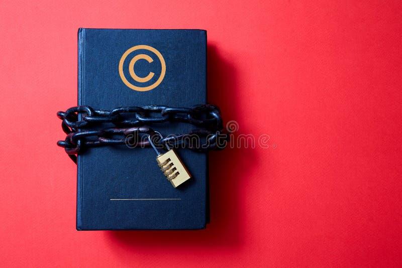 Concepto para los derechos reservados, patente o propiedad intelectual y protección de la idea El libro envolvió en una cadena co imagen de archivo
