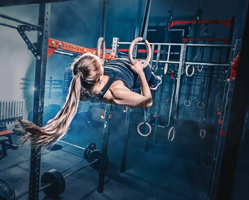 Concepto: poder, fuerza, forma de vida sana, deporte Mujer muscular atractiva potente en el gimnasio de CrossFit imagenes de archivo