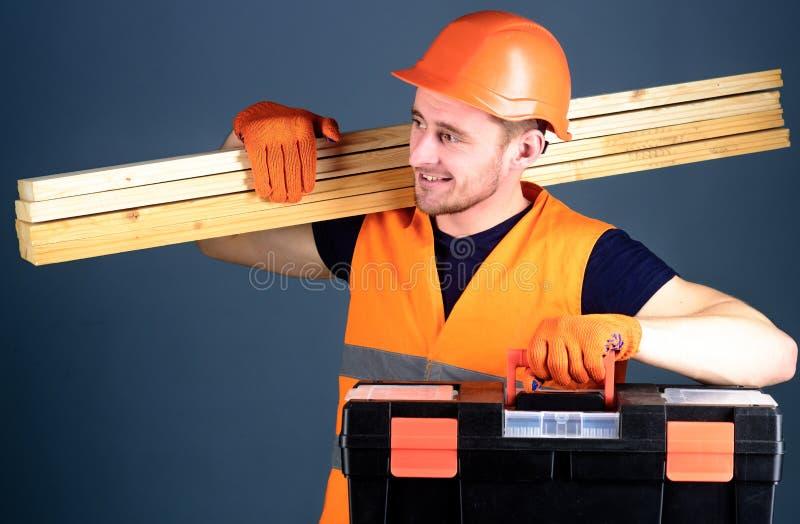 Concepto profesional del carpintero El hombre en el casco, casco lleva a cabo la caja de herramientas y los haces de madera, fond foto de archivo